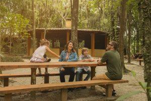 Família conhecendo o quiosque em meio a área verde do HIG