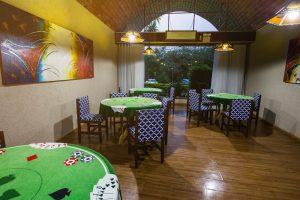 Sala de jogos com mesas redondas e ilustrada no estilo poker