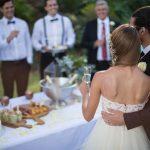 Noivos de costas olhando para a mesa e os convidados.