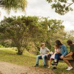 Família sentada em um banco na natureza